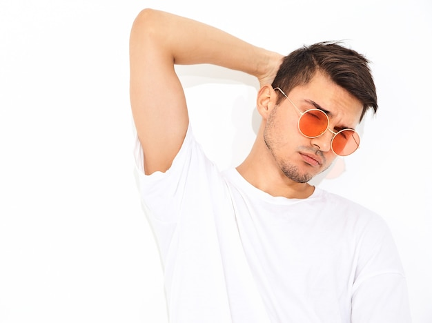 Portrait of handsome young model man dressed in jeans clothes  and t-shirt in sunglasses posing. touching his head Free Photo