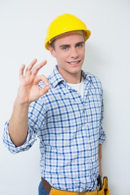 Portrait of a handyman in yellow hard hat gesturing okay sign Premium Photo