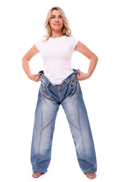 Portrait of happy aged woman wearing big jeans Free Photo