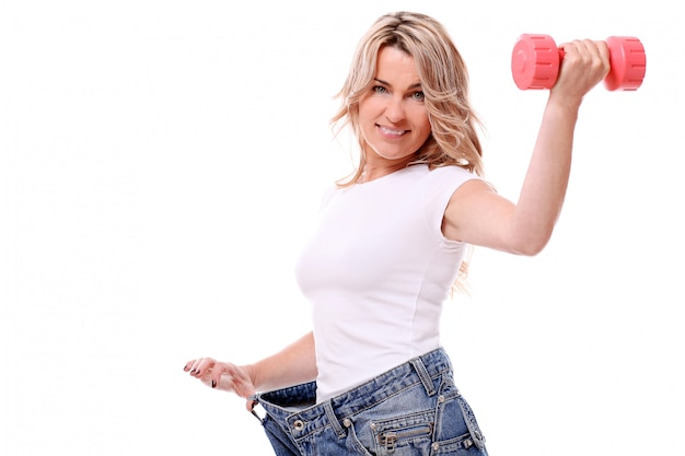 Portrait of happy aged woman with big jeans and dumbbell Free Photo