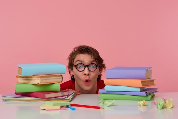 Ritratto di uomo felice stupito con gli occhiali indossa in maglietta rossa, nascosto al tavolo con i libri, guarda la telecamera con espressione sorpresa, sembra allegro, isolato su sfondo rosa. Foto Gratuite