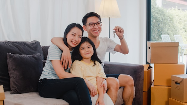 Portrait of happy asian young family bought new house. japanese little preschool daughter with parents mother and father holds in hand keys sitting on sofa in living room smiling looking at camera. Free Photo