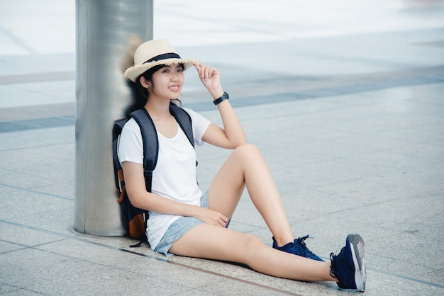 Portrait of a happy asian young woman sitting on the city Free Photo