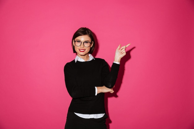 Portrait of a happy attractive businesswoman pointing Free Photo