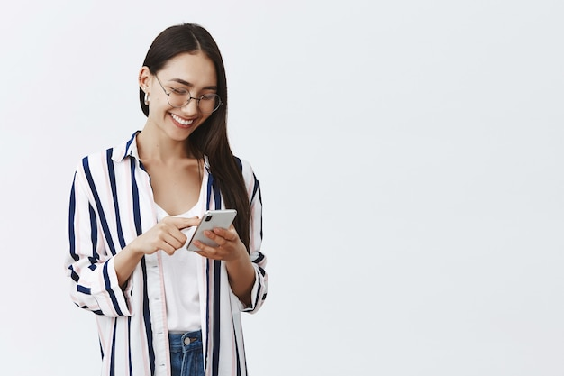 Portrait of happy attractive and stylish woman in glasses and striped blouse scrolling feed while using smartphone, reading amusing article in internet Free Photo