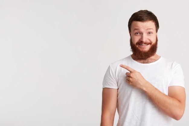 Ritratto di felice attraente giovane uomo hipster con barba indossa la maglietta sembra fiducioso e indica il lato a copyspace con il dito isolato sopra il muro bianco Foto Gratuite
