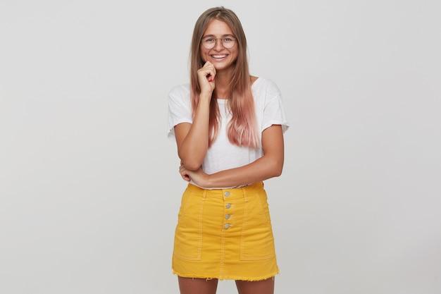 Ritratto di felice attraente giovane donna con lunghi capelli tinti rosa pastello indossa maglietta, gonna gialla e occhiali in piedi, sembra fiducioso e sorridente isolato sopra il muro bianco Foto Gratuite
