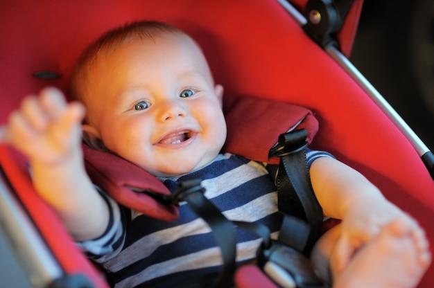 Portrait of happy baby boy in stroller Premium Photo