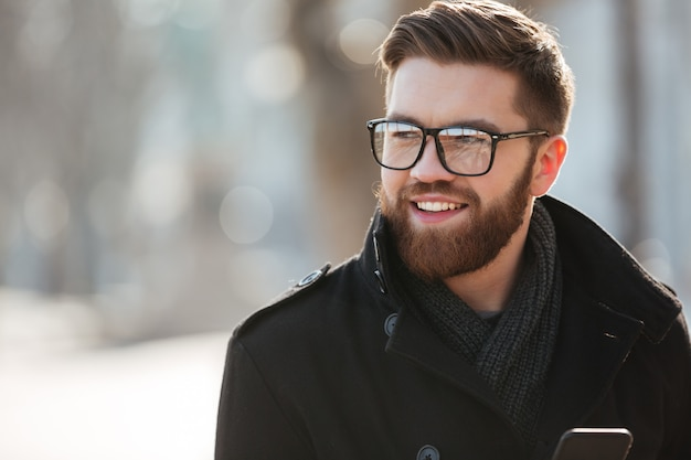 Portrait of happy bearded young man in glasses standing outdoors Free Photo