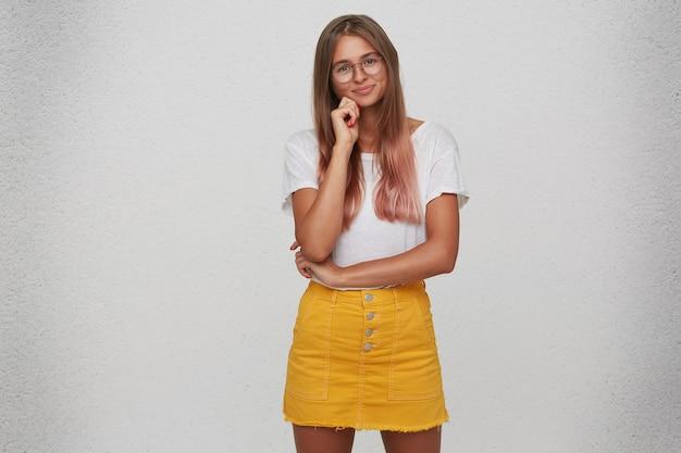 Ritratto di felice bella giovane donna indossa maglietta, gonna gialla e occhiali in piedi e tiene le mani giunte isolate sul muro bianco Foto Gratuite