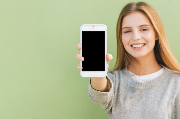 Portrait of a happy blonde young woman showing mobile phone against green backdrop Free Photo