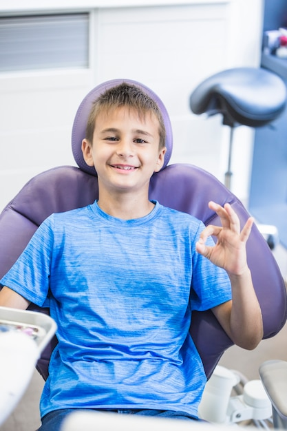 Portrait of a happy boy sitting on dental chair gesturing ok sign Free Photo