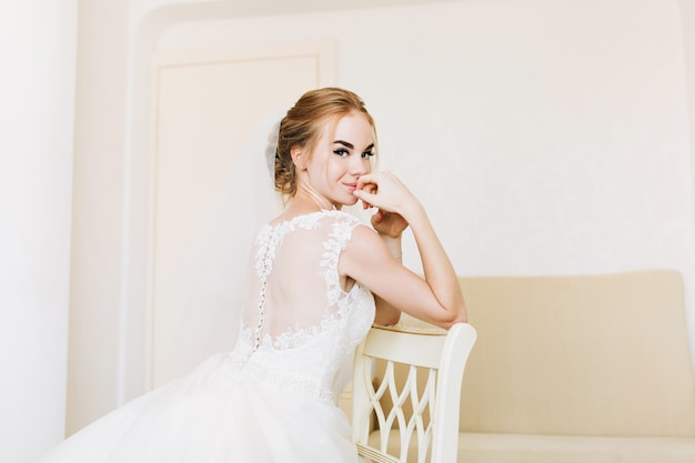 Portrait happy bride in wedding dress in appartment sitting on chair. Free Photo