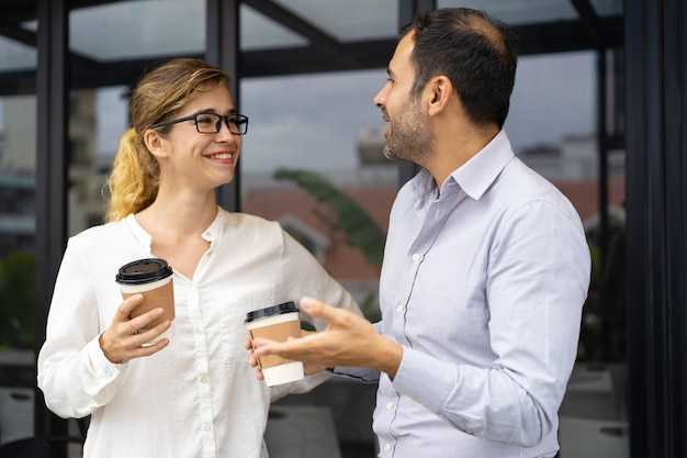 Portrait of happy business colleagues talking at coffee break Free Photo