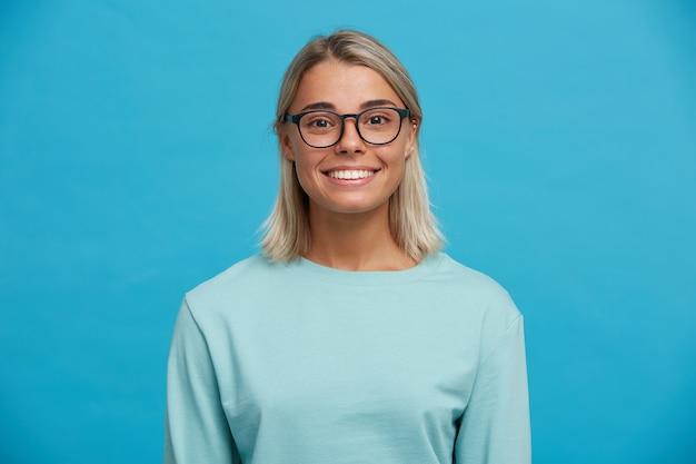 Ritratto di giovane donna bionda allegra affascinante felice in vetri, sorrisi Foto Gratuite