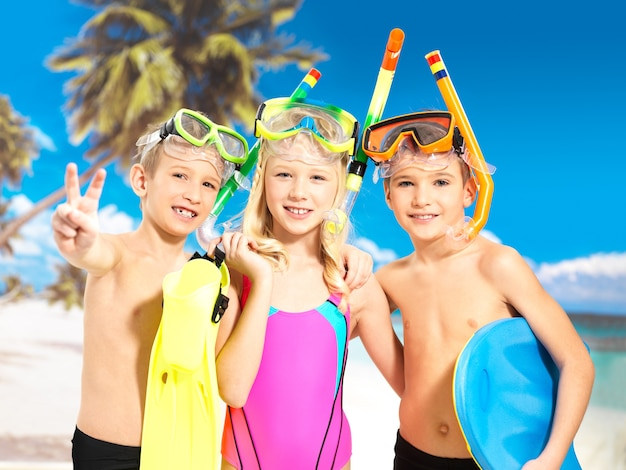 Portrait of the happy children enjoying at beach.  schoolchild kids standing together in bright color swimwear with swimming mask on head . Free Photo