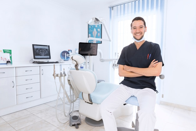 Portrait of a happy confident dentist in clinic Free Photo