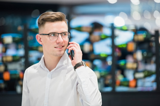 Portrait of a happy confident young businessman standing in bar talking on mobile phone Free Photo