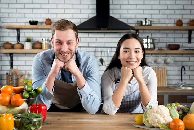 Portrait of happy couple looking at camera in their modern kitchen wearing apron Free Photo