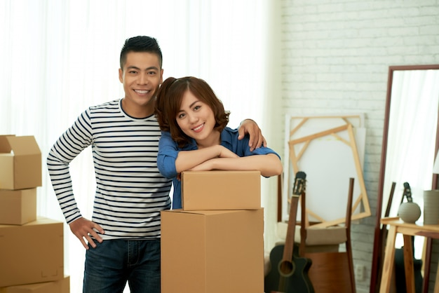 Portrait of happy couple posing at package boxes before relocation to the new apartment Free Photo