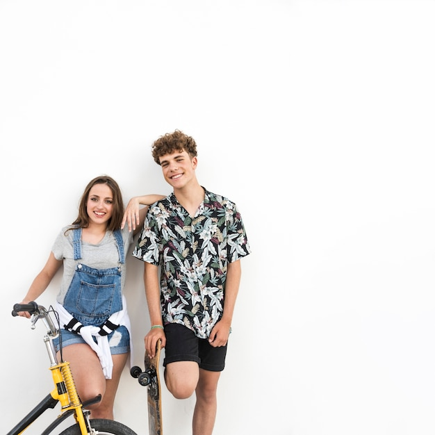 Portrait of a happy couple with bicycle and skateboard Free Photo