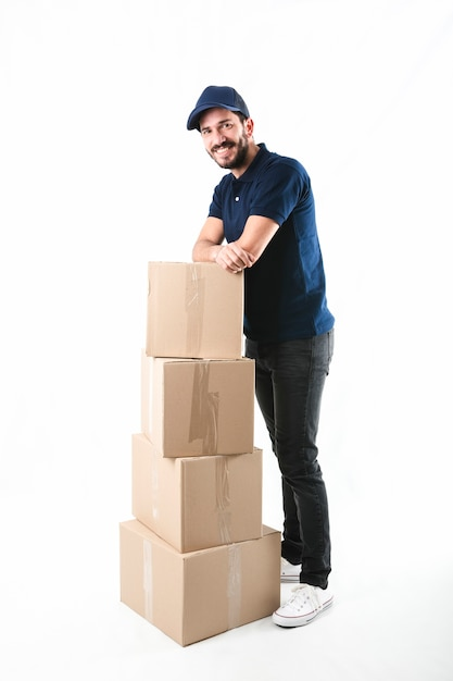 Portrait of a happy delivery man posing with stack of cardboard boxes Free Photo
