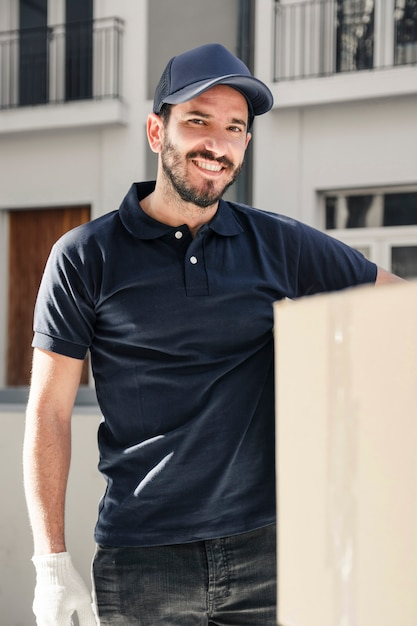 Portrait of a happy delivery man with cardboard box Free Photo