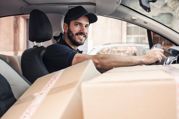 Portrait of a happy delivery man with parcels in vehicle Free Photo