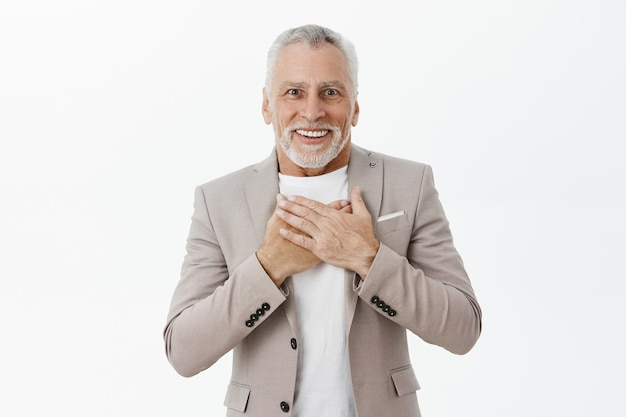 Portrait of happy excited senior man looking flattered and amazed, holding hands over chest Free Photo