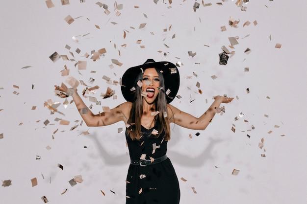 Ritratto di donna uscita felice che indossa un abito nero da sera e un cappello che lancia coriandoli sul muro isolato con vere emozioni felici. Foto Gratuite