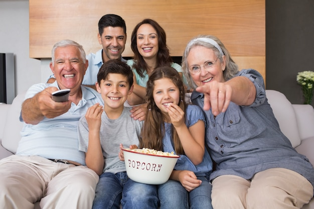 Portrait of happy extended family watching tv in living room Premium Photo