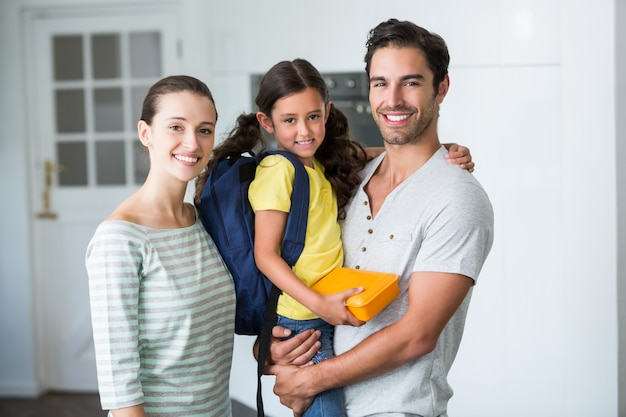 Portrait of happy family with daughter holding lunch box Premium Photo