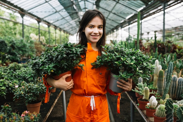 Portrait of a happy female gardener holding two potted plants Free Photo