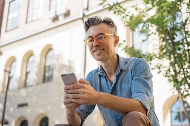 Portrait of happy freelancer receive payment sitting in park. Premium Photo