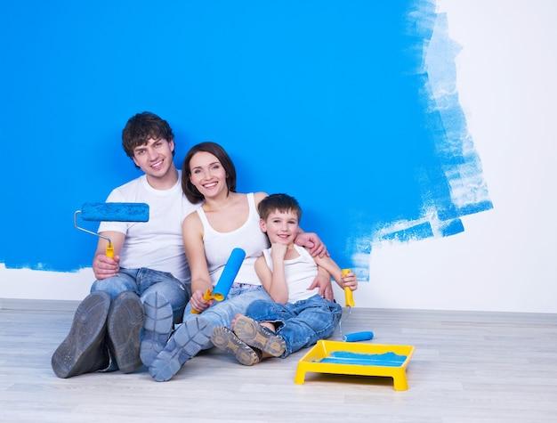 Ritratto della famiglia amichevole felice che si siede sul pavimento con il pennello Foto Gratuite