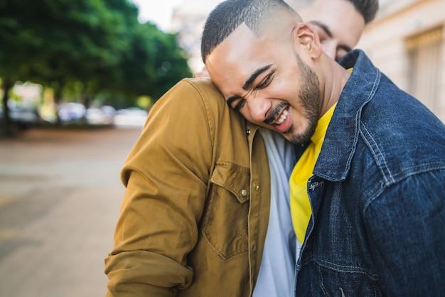 Ritratto di felice coppia gay di trascorrere del tempo insieme e abbracciando in strada. lgbt e concetto di amore. Foto Gratuite