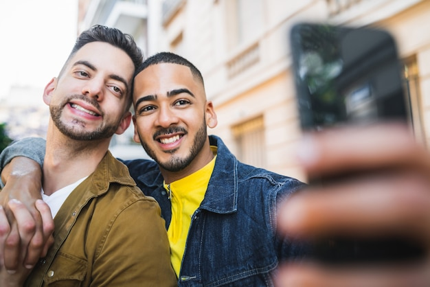 Portrait of happy gay couple spending time together and taking a selfie with mobile phone in the street. Free Photo