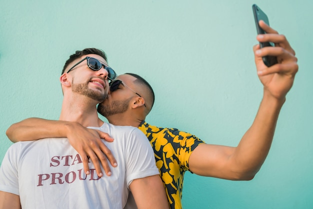 Portrait of happy gay couple spending time together and taking a selfie with mobile phone. Free Photo