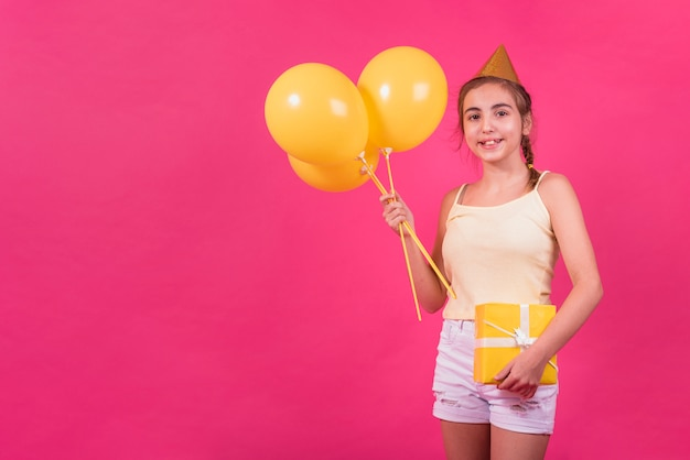 Portrait of a happy girl holding yellow gift box and balloons in her hand over pink background Free Photo