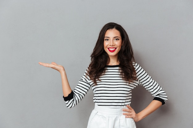 Ritratto di una ragazza felice in piedi con il braccio sui fianchi Foto Gratuite
