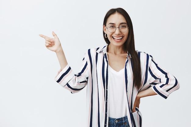 Ritratto di felice bella donna d'affari femminile in orecchini e bicchieri, tenendo la mano sul fianco e mostrando a sinistra Foto Gratuite