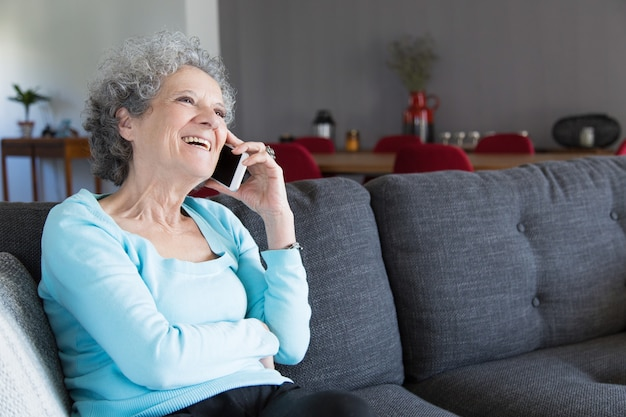 Portrait of happy grandma sitting on sofa and talking on phone Free Photo
