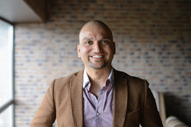 Portrait of happy handsome indian business man, smiling, confident and friendly indoors. Premium Photo