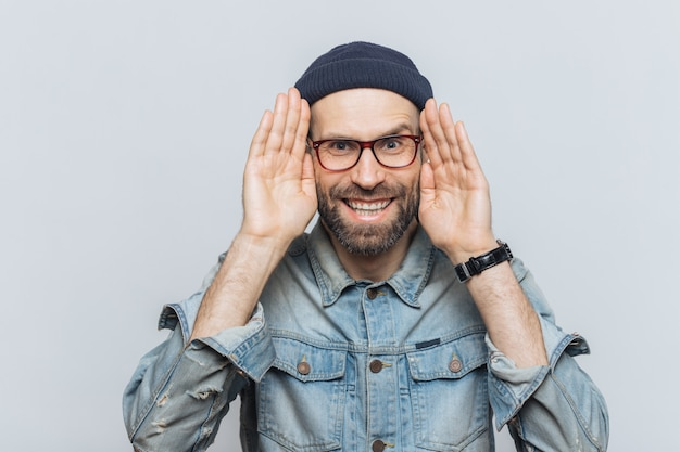 Portrait of happy hipster guy with thick beard and mustache wears stylish hat and glasses Premium Photo