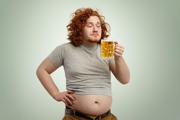 Ritratto di uomo di zenzero gioioso felice che gode dell'odore di birra chiara schiumosa fredda nelle sue mani Foto Gratuite