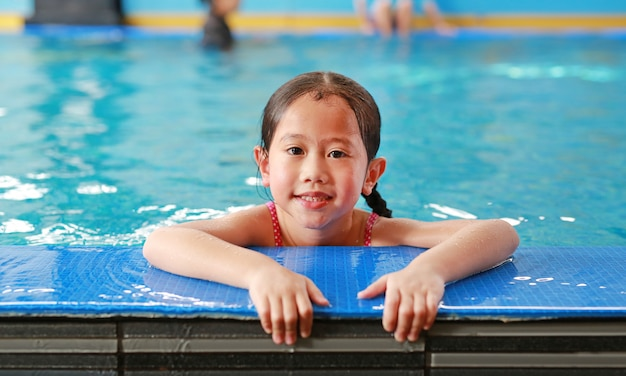 Portrait of happy little asian child girl learning to swim in pool. close-up short. Premium Photo