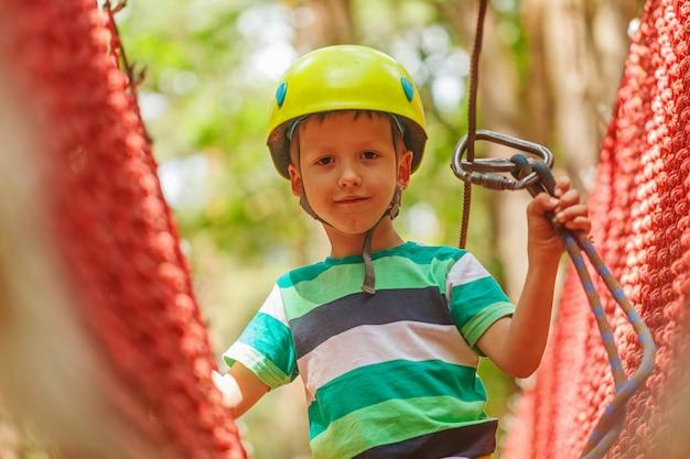 Portrait of happy little boy having fun in adventure park smiling to camera wearing helmet Premium Photo
