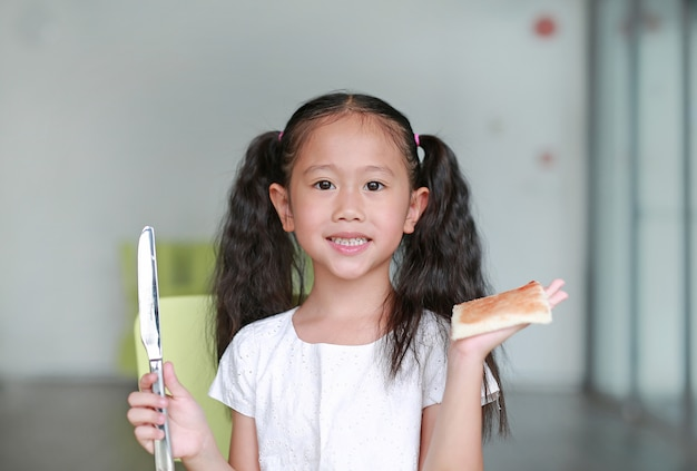Portrait happy little child girl cooking at class room. children show an apply strawberry jam on bread. Premium Photo