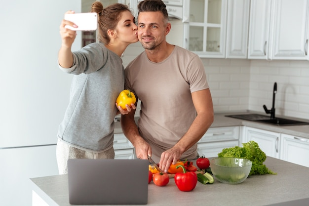 Portrait of a happy loving couple cooking salad together Free Photo
