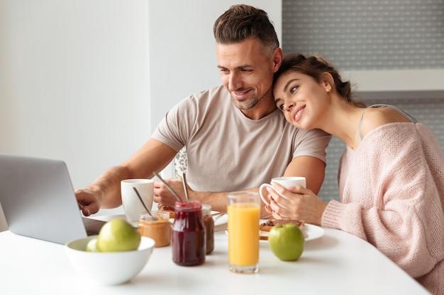 Portrait of a happy loving couple having breakfast Free Photo